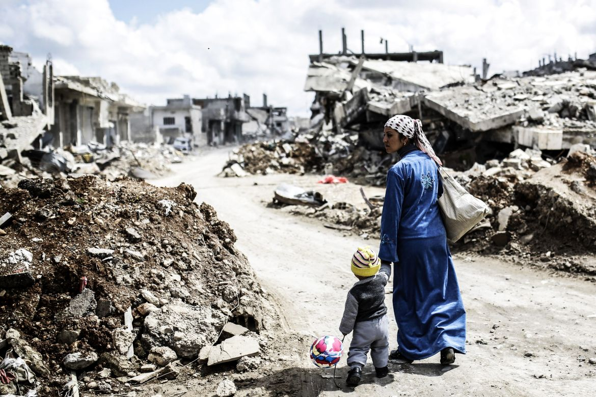 A Kurdish Syrian woman walks with her child past the ruins of the town of Kobane, also known as Ain al-Arab, on March 25, 2015. Islamic State (IS) fighters were driven out of Kobane on January 26 by Kurdish and allied forces. AFP PHOTO/YASIN AKGUL        (Photo credit should read YASIN AKGUL/AFP/Getty Images)